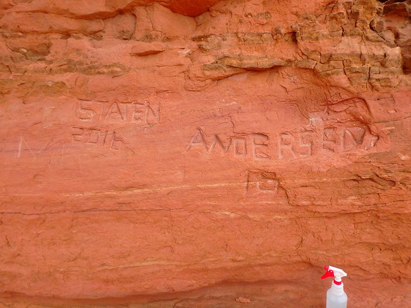 This National Park Service photograph shows carved graffiti at Frame Arch at Arches National Park.