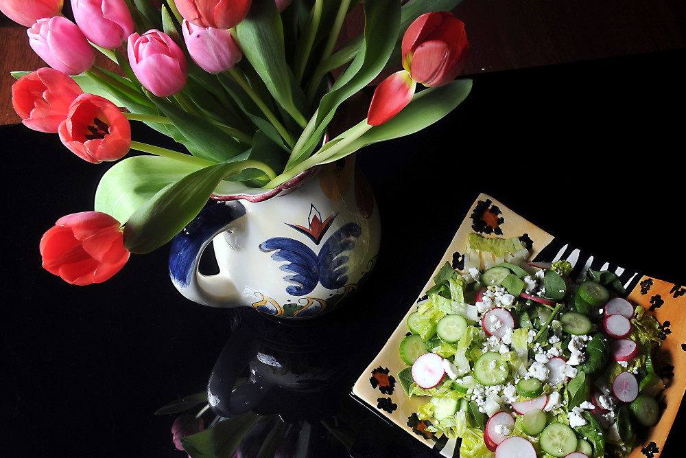 Tulips adorn a table with a spring salad with spinach, romaine lettuce, radish and cucumber, served with a creamy mint dressing.