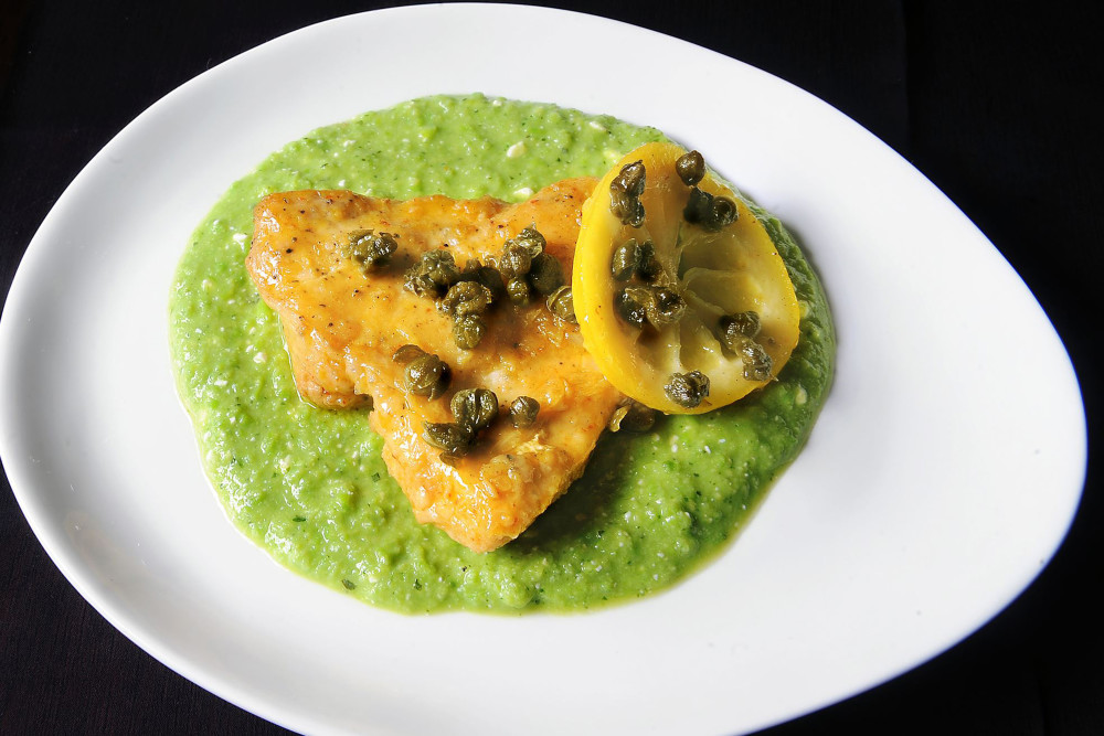 """Sauteed lemon chicken and fried capers from """"Sara Mouton's Home Cooking 101"""" sits on sweet pea puree that has a slight kick."""