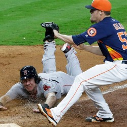 Boston Red Sox's Ryan Hanigan slides into home to score from third base on a wild pitch by Houston Astros' Ken Giles (53) in the 12th inning of a baseball game in Houston. Boston won 8-5.  The Associated Press