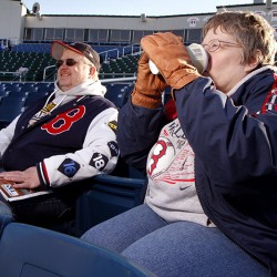 "Carl D. Walsh/Staff Photographer: Sea Dogs fans Don and Ann McNeil of Old Orchard Beach drink hot chocolate before Portland Sea Dogs 2011 home opener at Hadlock Field on Thursday April 7, 2011.  Ann, wearing gloves, said ""At least it is not snowing""."
