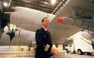 Brunswick Naval Air Station's then-commanding officer, Commander Frank V. Klein, discussed the new role of the P-3 Orion, equipped with new electronics and Maverick missiles, shown under its wing, in a hangar at the air station.