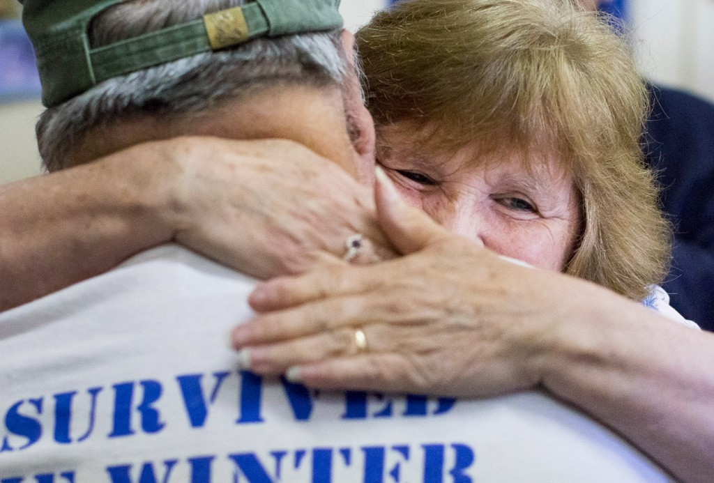 Marie Andrews hugs her husband, Dennis Andrews of Boothbay Center after he received a Bronze Star Medal and a flag that had flown over the White House.