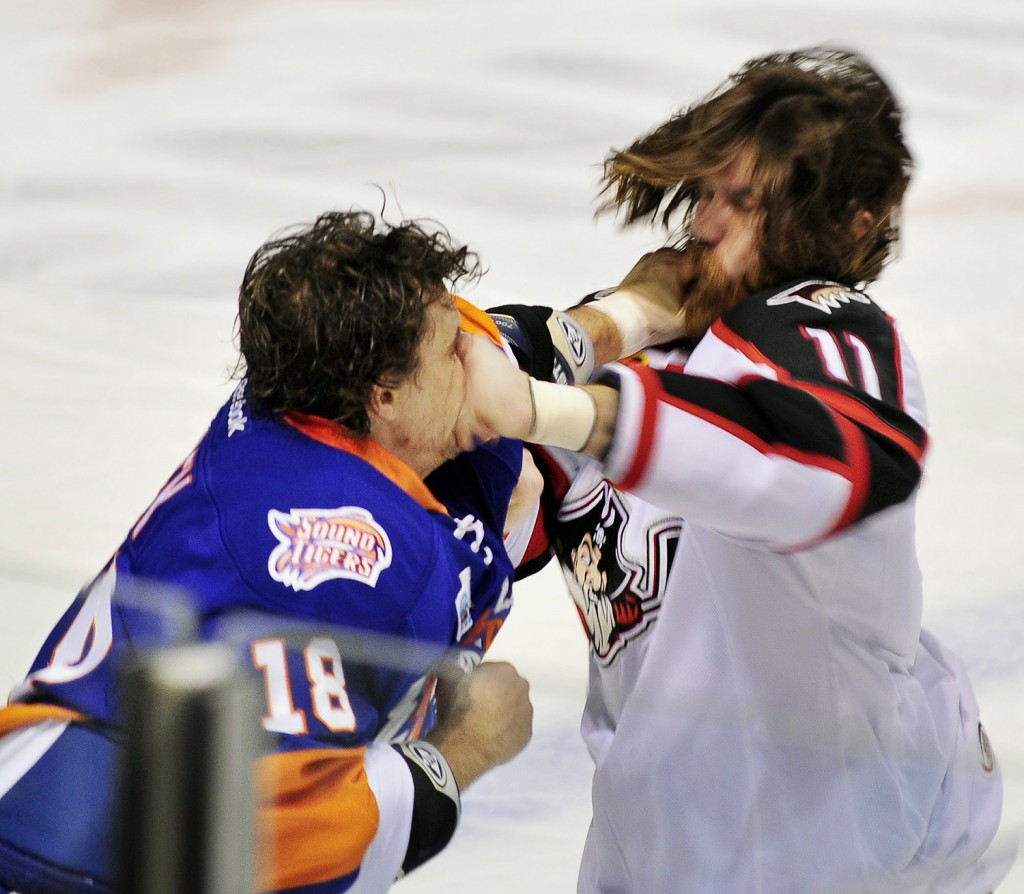 Gordon Chibroski / Staff Photographer.  Friday, February 3, 2012. Bridgeport #18, Michael Haley and Portland #11, Ryan Hollweg trade punches in a fight in first period AHL hockey action: Portland Pirates host the Bridgeport sound Tigers at the CCCC.