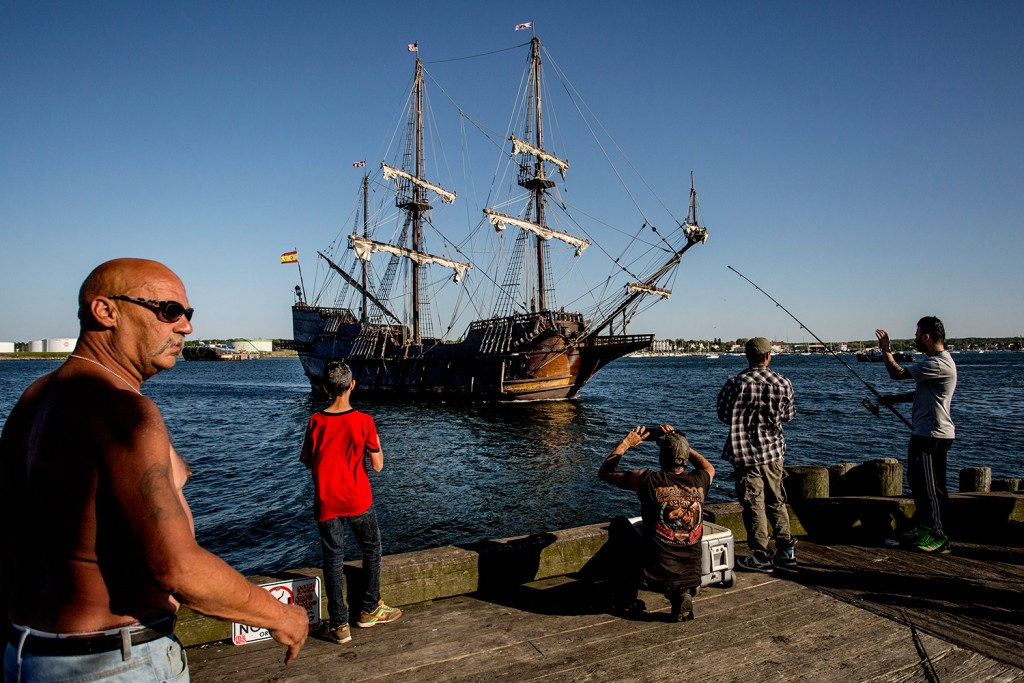 Fishermen on the Maine State Pier take pictures of the El Galeon as it comes in under motor power.