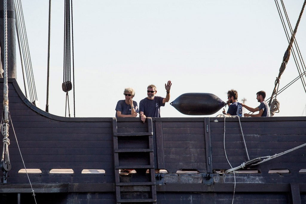 Crew members wave from aboard the El Galeon as it sails past the Maine State Pier on its way to the Maine Wharf.