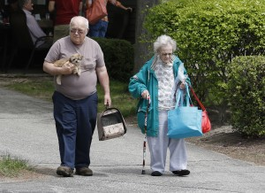 Barbara Cash, right, a resident at the Oxford Meadow Apartments, returns with her son-in-law, left, who declined to give his name, and her dog, Lily, to pick up some belongings on Saturday following an early morning fire in Oxford. Joel Page/Staff Photographer