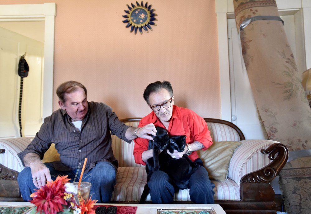 Brian Aldo Baldie cuddles with his cats, Mary and Joseph, as his husband, Ron Pelletier, pats them on the head while at their new apartment recently. Staff photo by Michael G. Seamans