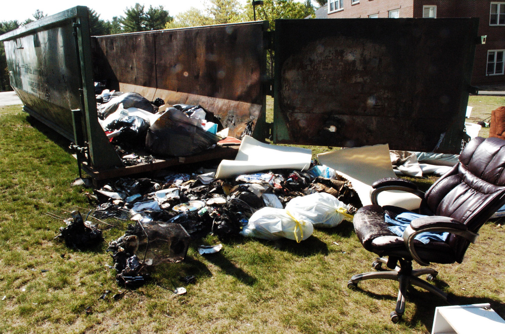 Furniture and other items that were burned last weekend damaged a Dumpster outside the Alfond dormitory on the Colby College campus in Waterville.