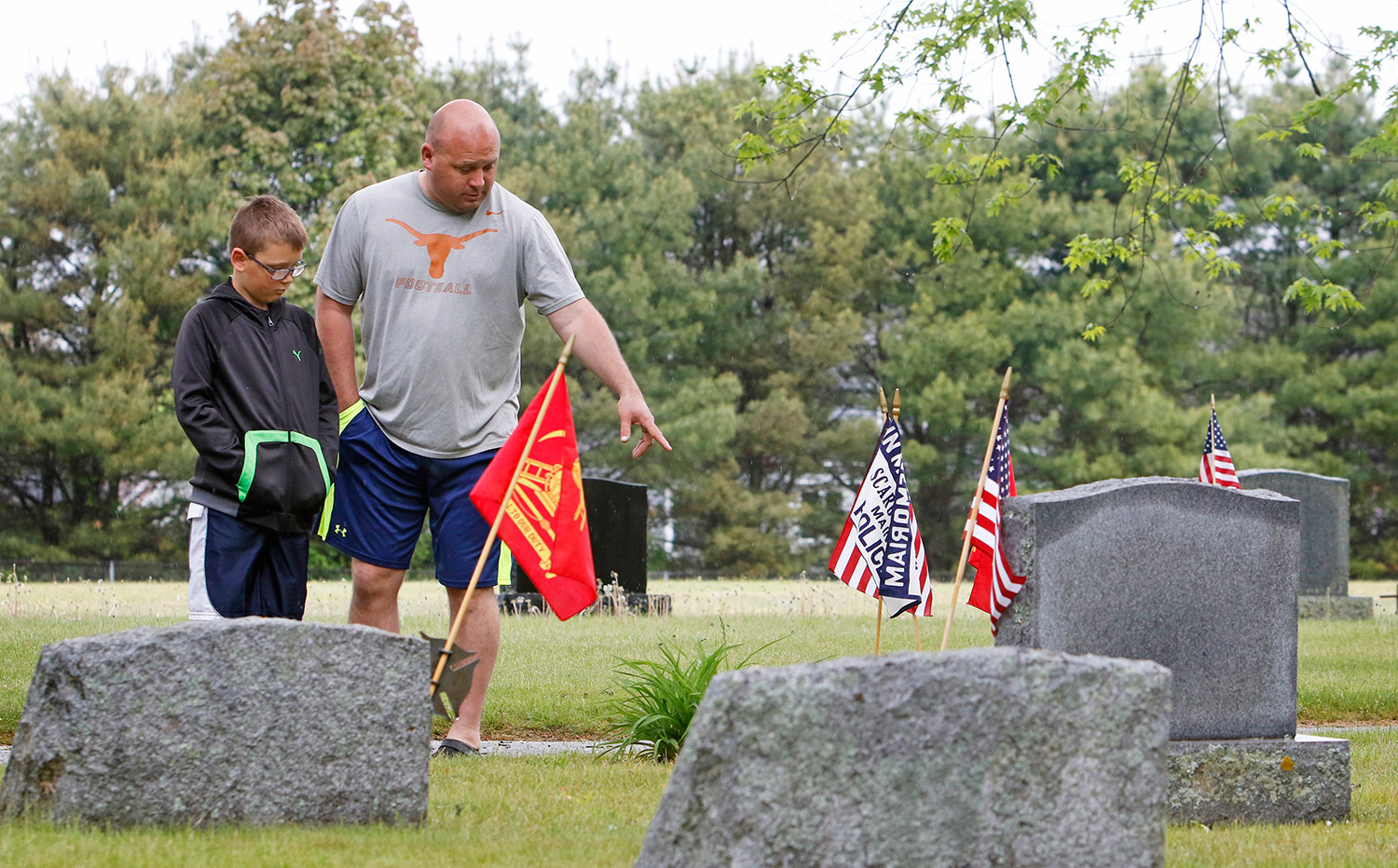 Jason Greenleaf and his son, Jackson, 9, explore Black Point Cemetery following a Memorial Day service in Scarborough. Jason, who is a Scarborough firefighter, says both sides of the family include police officers and firefighters that are buried at Black Point.