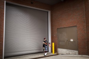 PORTLAND, ME - MAY 22: Brendan Murphy of Topsham, a bagpipe player with the Maine Public Safety Pipe & Drum Corps, adjusts his bagpipes outside a loading dock at the Cross Insurance Arena before playing at Southern Maine Community College's 69th annual graduation ceremonies at the Cross Insurance Arena in Portland Sunday, May 22, 2016. The school graduated nearly 1,100 students. (Photo by Gabe Souza/Staff Photographer)