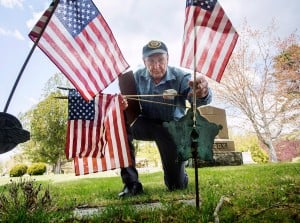 Ralph Bonville, 97, of Falmouth Memorial Post 164, removes a flag from a gravesite at Pine Grove Cemetery. Bonville was checking the grave sites to ensure that each war veteran had a flag and that they were in the right locations. He said often the flags get moved, or placed at the wrong stone. Last year the veterans placed 1,369 flags in cemeteries in Falmouth, where they stay until Veterans Day.