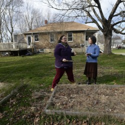 Lisa Fernandes, founder and executive director of The Resilience Hub, consults with new gardener Peggy Grodinsky.