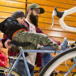 Logan Hychko, 6 of South Portland, sits on the seat as his father John pushes a bike to test drive at 16th annual Bike Swap at USM in Portland on Sunday, May 1, 2016. Sponsored by the Bicycle Coalition of Maine, over one thousand bikes were available for sale, by individuals and dealers, and over 2000 people were expected to attend, according to Bicycle Coalition of Maine Communications Director Brian Allenby. Proceeds of sales, an estimated $ 125,000  go back into the pockets of sellers, with a 15% commission going to support the mission of the coalition to make the riding and walking experience better in the state. (Photo by Carl D. Walsh/Staff Photographer)