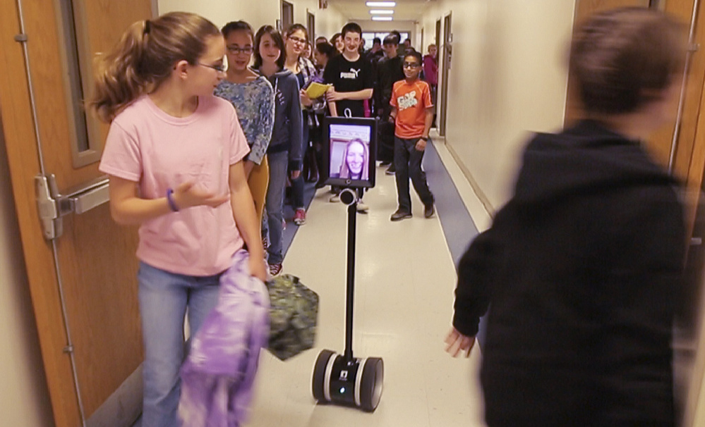 """This photo from video shows the robot nicknamed """"Double"""" with Abby Fisher's image in a hallway at the Vassalboro Community School."""