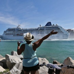 A woman from Cuba waves Adonia leaves port in Miam en route to Cuba.