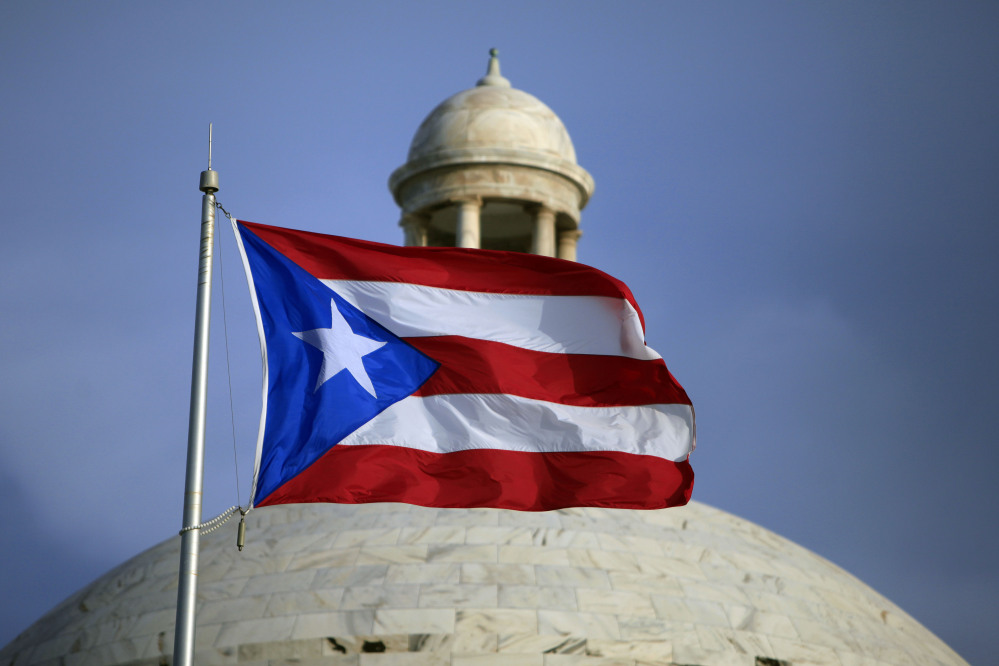 In this Wednesday, July 29, file 2015 photo, the Puerto Rican flag flies in front of Puerto Rico's Capitol as in San Juan, Puerto Rico.