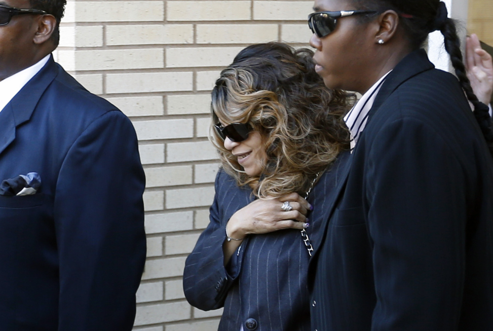 Tyka Nelson, center, the sister of Prince, is escorted by unidentified people as she leaves the Carver County Courthouse Monday in Chaska, Minn. where a judge has confirmed the appointment of a special administrator to oversee the settlement of Prince's estate.