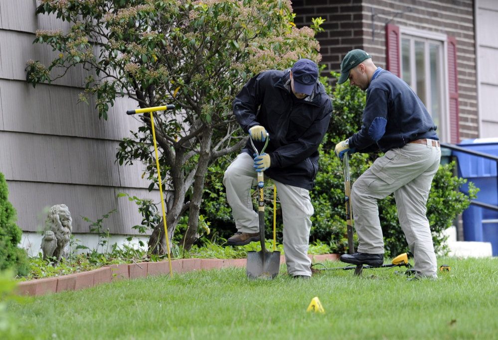 Law enforcement agents dig in the front yard of the home of Robert Gentile in Manchester, Conn., during a previous visit. Agents returned to the house Monday.