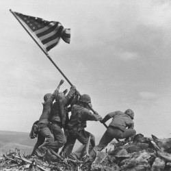 U.S. Marines of the 28th Regiment, 5th Division, raise the American flag atop Mount Suribachi on Iwo Jima in this famous photo taken on Feb 23, 1945.