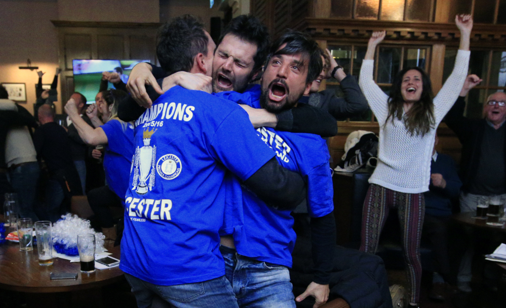 Leicester City fans roar their approval in Hogarths public house in Leicester, England, after a 2-2 Chelsea-Tottenham tie Monday gave Leicester City the Premier League title.
