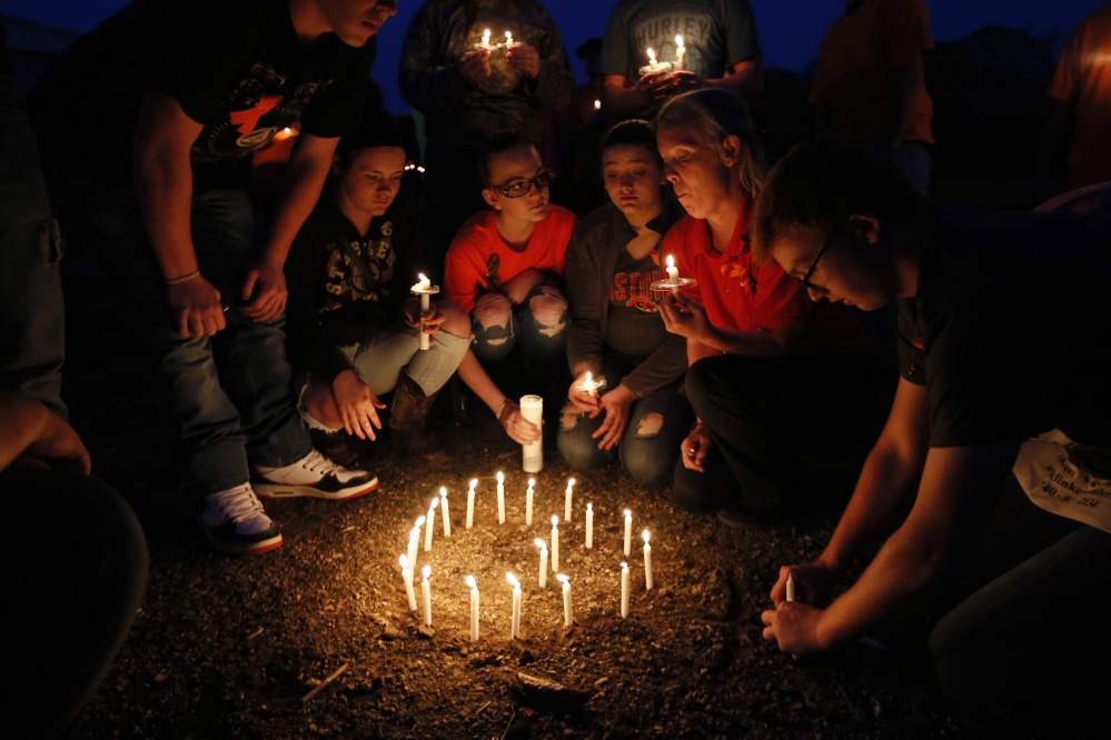 Jacob Hoagland, right, places candles into the ground to form a G during the Pike County Vigil at the Pike County  Fairgrounds in Piketon, Ohio on Friday.