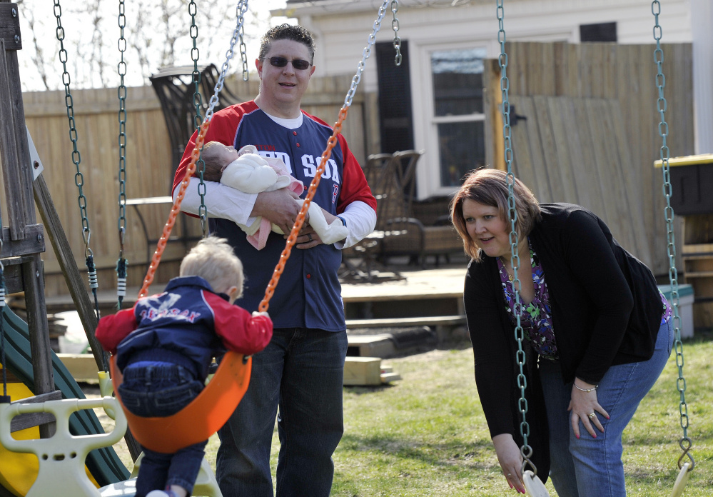 Kevin Cunningham holds his 6-week-old daughter, Bailey, as his wife Jill pushes their son Jameson 2, on the swings at their Lewiston home. Cunningham was the executive chef at The Inn at Brunswick Station.