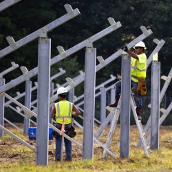 Workers for RBI Solar Inc. install supports for solar panels on land owned by Bowdoin College at the former Brunswick Naval Air Base. The 1.2-megawatt array is now the largest in Maine, but Yarmouth-based Ranger Solar plans a 50-megawatt array in Sanford.