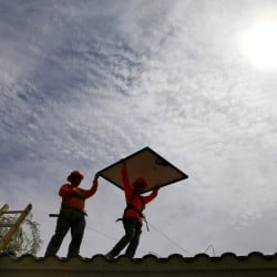 In this July 28, 2015, photo, electricians Adam Hall, right, and Steven Gabert, install solar panels on a roof for Arizona Public Service company in Goodyear, Ariz. Thanks to falling prices, investment in solar and wind power projects has outpaced investment in fossil-fueled power plants for the second straight year, according to the U.S. Department of Energy.