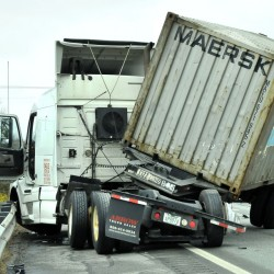 Driver Paul Cusano surveys the scene after his tractor-trailer jackknifed in the northbound lanes of the Interstate 95 overpass near Kennedy Memorial Drive in Waterville on Thursday.