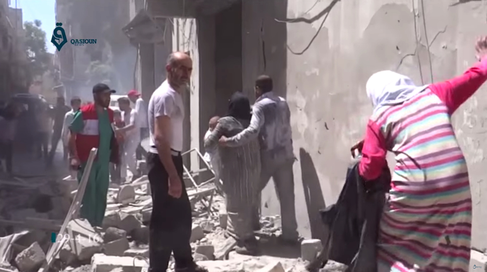A photo from Friday shows people scrambling through rubble following airstrikes in Aleppo, Syria. The northern city has been the center of violence in recent weeks.