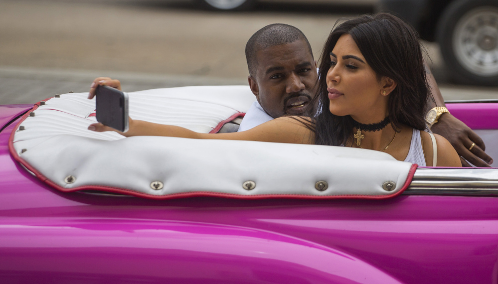 American reality-show star Kim Kardashian takes a selfie as she rides in a classic car next to her husband, rapper Kayne West, in Havana on Wednesday.
