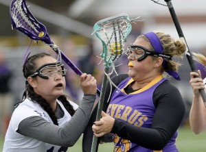 Julia St. John of Cheverus, right, drives to the net Thursday as Cindy Hoang defends for Deering during their girls' lacrosse game at Deering High. Cheverus came away with an 8-7 victory.