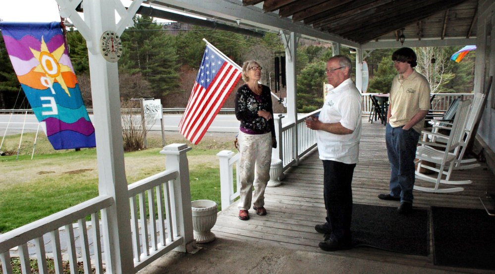 Sterling Inn owner Eric Angevine, center, speaks with house painter Lou Kifer on the porch of the inn in Caratunk recently. Angevine's son, Zachary, is at right.