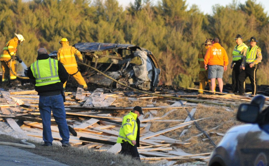 Police and firefighters work on March 18 at the scene of the multi-vehicle crash on Route 17 in Washington. A truck driver has been arrested in Virginia and charged in connection with the crash, which killed two people.