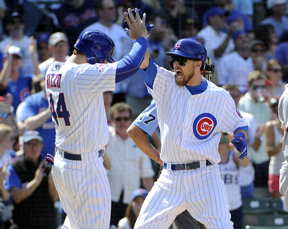 The Cubs' Ben Zobrist, right, is greeted by Anthony Rizzo after Zobrist's three-run homer against the Nationals during an 8-6 Chicago win Friday.