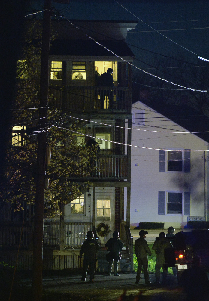 Police enter the apartment building where a third-floor tenant set fire to himself Monday night after a six-hour standoff.