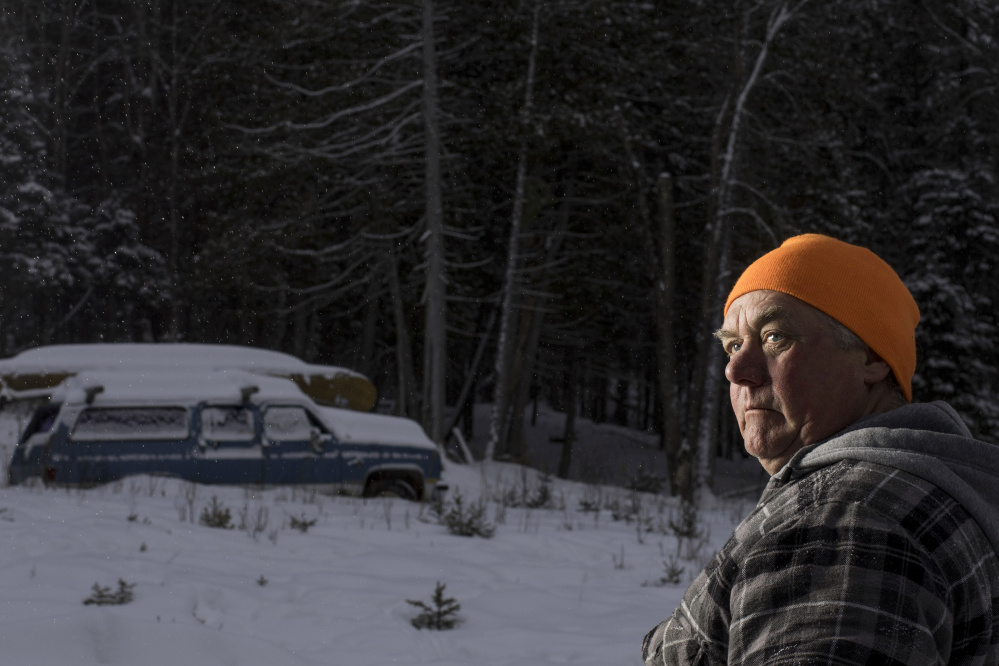 Carter McBreairty, 56, stands outside his Allagash home near dusk. Unaware that a visitor to the area was an undercover agent, McBreairty allowed the man who was investigating him to stay in his house for days, even when McBreairty was at his construction job in midcoast Maine.