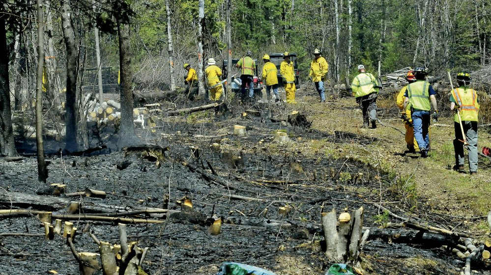 A large turnout of firefighters from many area departments battle a wind-driven woods fire off Route 43 in Starks on Wednesday.