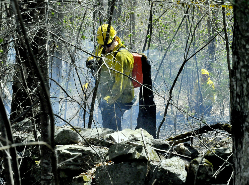Wilton firefighter Brett Osgood uses a portable water tank to fight a wind-driven woods fire Wednesday on Route 43 in Starks. Numerous area fire departments showed up to put out the flames. Fire danger has been higher than normal this spring in central Maine.