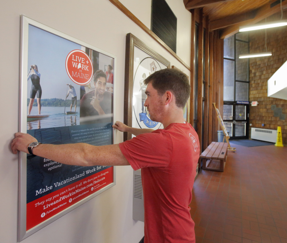 Nate Wildes of Live + Work in Maine puts up a poster at the visitors' center in Kittery. Posters also have been installed at the Portland International Jetport to tout the program.