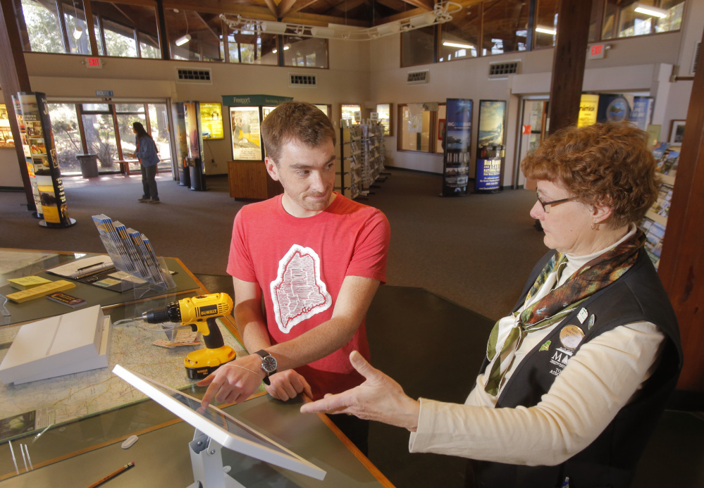 Nate Wildes explains the Live + Work in Maine iPad to Marcia Peverly, manager of the visitors' center in Kittery, where the kiosk gives the program exposure to many of the 34 million people who visit the state each year.