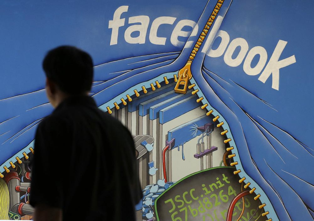 A man walks past a mural in an office on the Facebook campus in Menlo Park, Calif. On Thursday, the company released details of how items are chosen for its Trending Topics feature and says it has a system of checks and balances to prevent bias.
