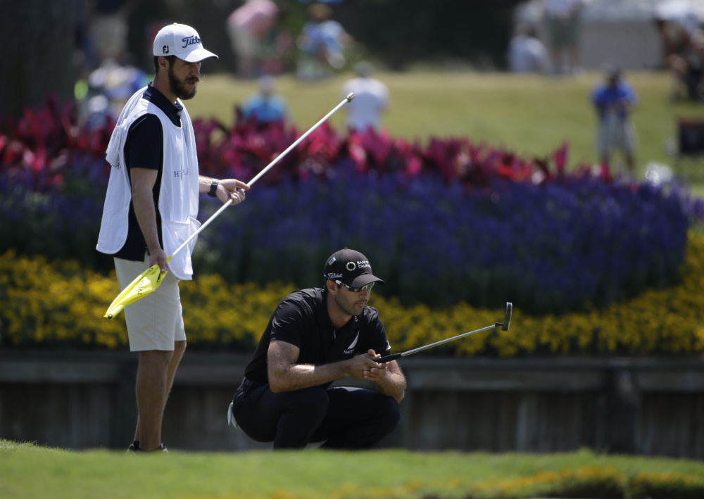 Cameron Tringale and his caddie, Carl Smith, look at Tringale's shot on the 17th green during the first round of The Players Championship in Ponte Vedra Beach, Fla., on Thursday. Tringale was one of five players two strokes back at 7-under 65 after an unusually forgiving day at TPC Sawgrass.