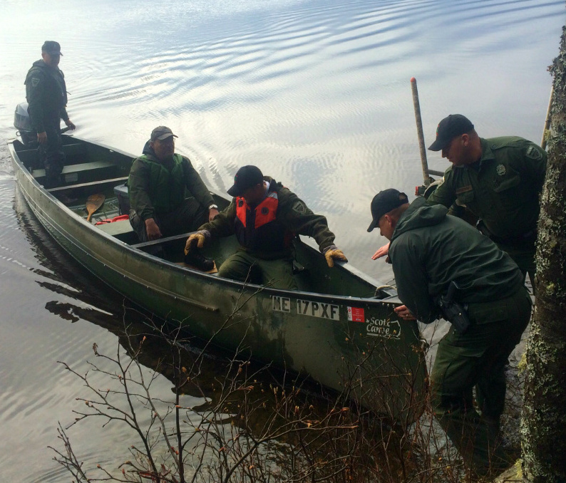 Game wardens pull a canoe ashore with Mike Jones, who spent the night in a remote camp on Grand Lake Seboeis.