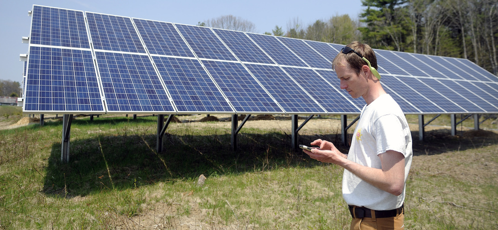 Hans Albee, an engineer at ReVision Energy, at the Sky Ranch Solar Farm in Wayne on Thursday. Nine Central Maine Power customers collectively contributed $200,000 to have the photovoltaic panels installed.