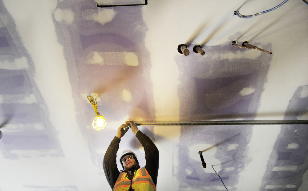 Sy Kottmann of the mechanical contractor Johnson & Jordan prepares a room for a hot water tank Monday at the Downeaster layover station being built in Brunswick.