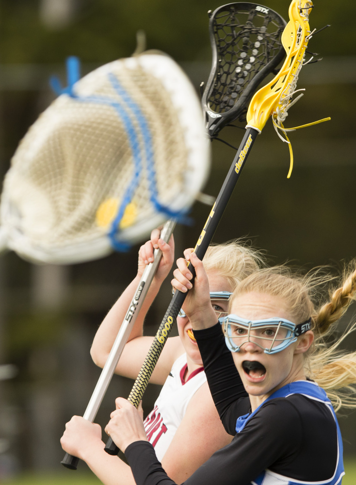 Morse's Mae Winglass, right, watches as Freeport's Lindsay Cartmell winds up for a shot on goal in Monday's girls' lacrosse game at Freeport. Morse won 7-6 in overtime.