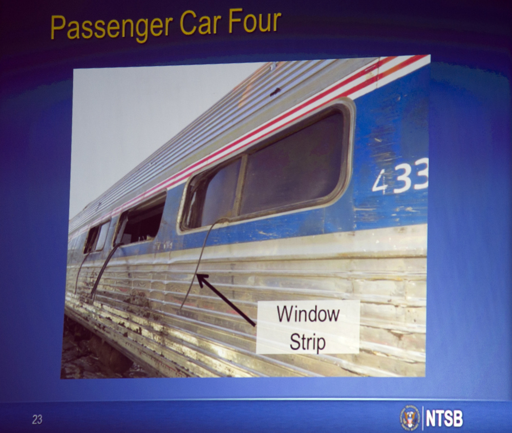 A photograph displayed on a video monitor shows a window that separated from the train car during the derailment of an Amtrak passenger train in Philadelphia last year, during a National Transportation Safety Board meeting on the derailment Tuesday in Washington.