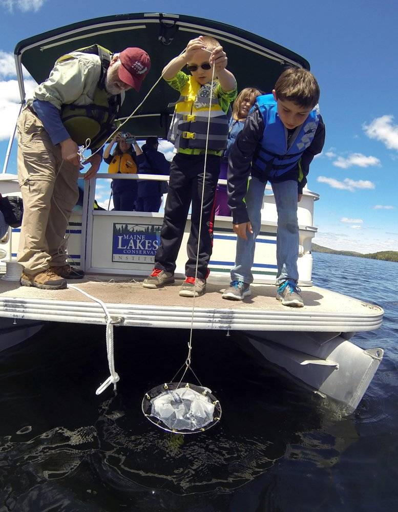 Peter Kallin, left, Noah Easter and Cobey Dunn drop a net to collect plankton Wednesday on board the Maine Lakes Society's floating classroom on Great Pond in Belgrade.